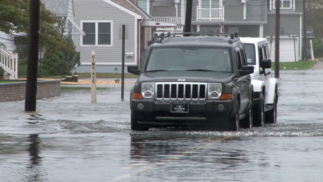 One vehicle pushes another stalled out vehicle through flood waters during a noreaster along the Jersey Shore