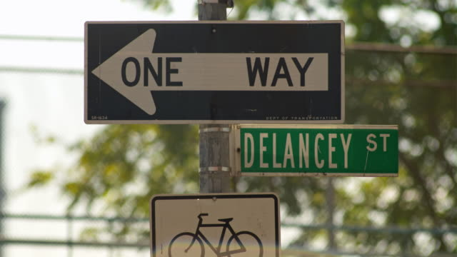 a one way sign flaps in the wind.  street signs of bike lane and delancey street - one way stock videos & royalty-free footage