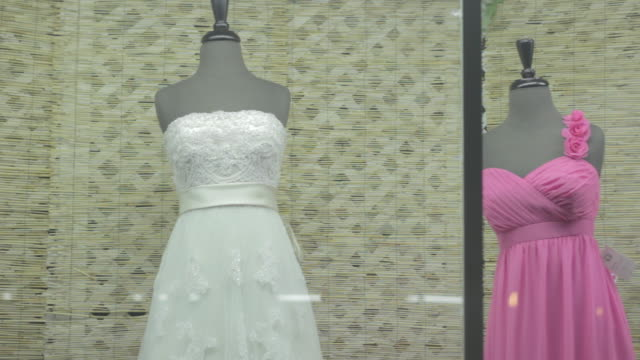 vídeos de stock, filmes e b-roll de one wedding dress and three bridesmaid's dresses in a storefront window at night. - bridesmaid