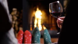 One winter evening a couple sitting in front of the fireplace relaxing, drinking a glass of wine and making a toast while enjoying the warmth of the fireplace. Concept of: holidays, relaxation, wine.