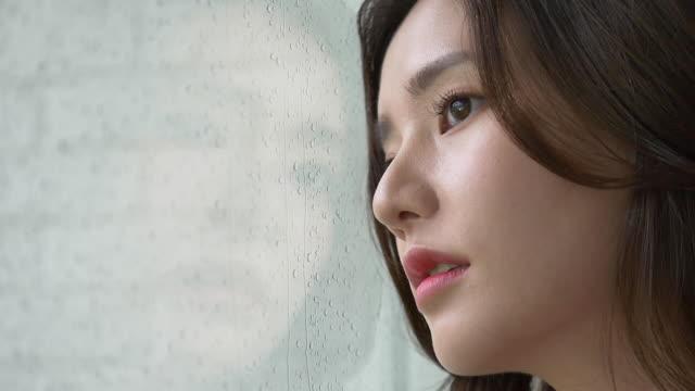 vidéos et rushes de one woman deep in though looking out rainy window - nostalgie