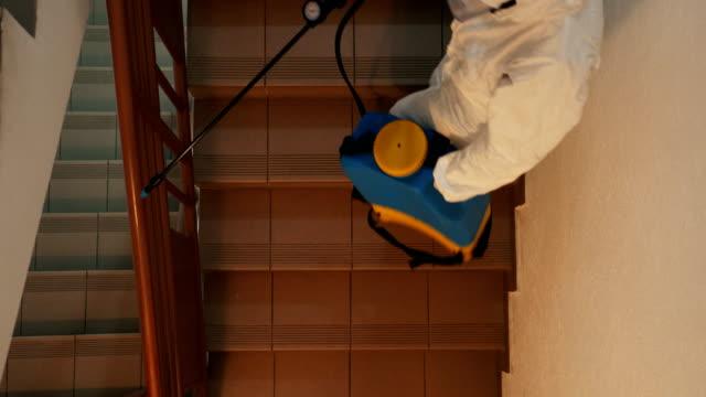 住宅用建物スペースを消毒する防護服を着た女性1人 - クリーンスーツ点の映像素材/bロール