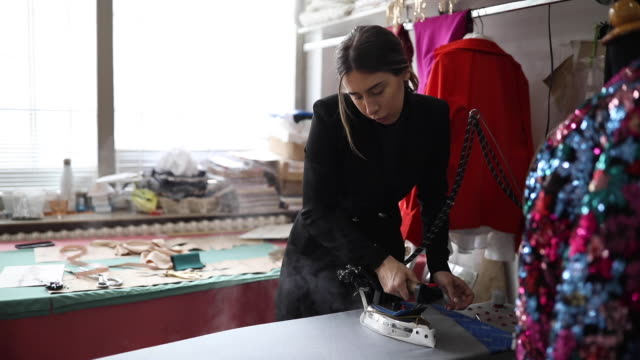 one woman ironing cloth in the tailor shop - fashion designer stock videos & royalty-free footage