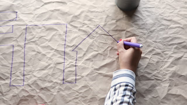 One woman is drawing building and trees on a crumpled paper