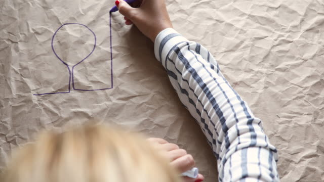 one woman is drawing building and trees on a crumpled paper - crumpled paper stock videos and b-roll footage