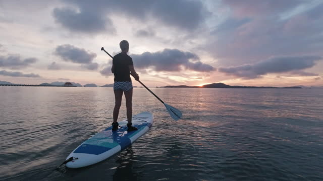 vidéos et rushes de one woman learning to paddle board at sea beautiful sunrise - 45 49 ans
