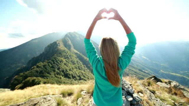 Eine Frau machen Herzform am mountain top
