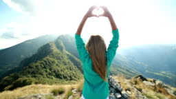 One woman making heart shape at mountain top
