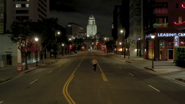 one woman running alone on empty city street at night - quarantena video stock e b–roll