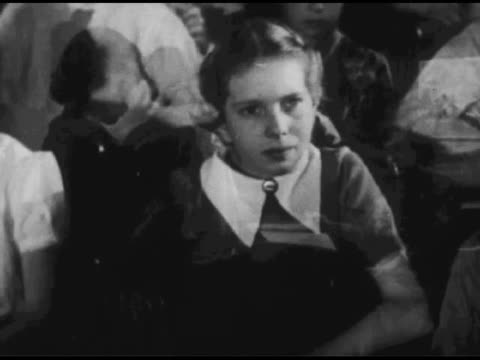 vídeos de stock, filmes e b-roll de / one woman sits at desk and writes in notepad; two children and another woman stand / panning shot of children in theater / reverse shot of theater... - 1951