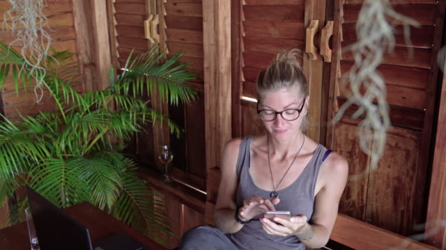 one woman using smart phone in indoor garden area - reading glasses stock videos & royalty-free footage