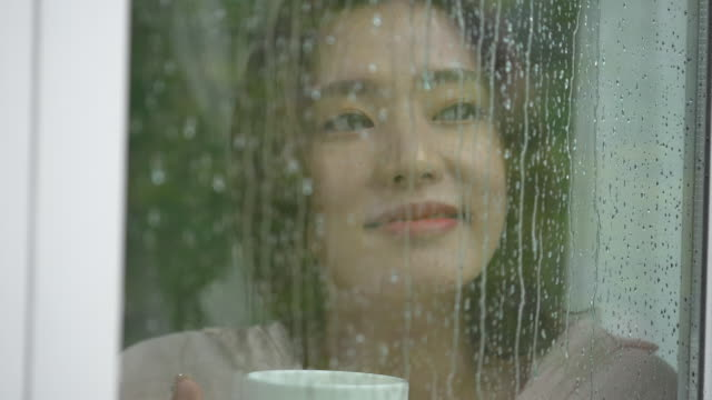 one woman with cup looking out rainy window - looking through window stock videos & royalty-free footage
