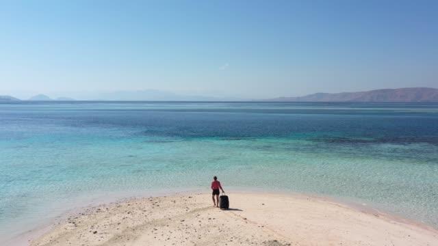 vidéos et rushes de une femme avec des bagages à roues sur le bord de l'île rose tropicale utilisant le téléphone - tropical