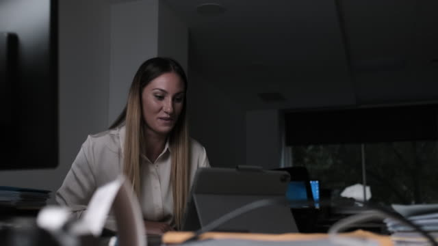 one woman working late at night at the office. - small office stock videos & royalty-free footage