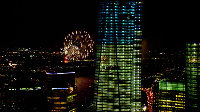 aerial close up one world trade center and 7 world trade center with fireworks over hudson river in background at night, zoom out to wide shot with world financial center - manhattan stock-videos und b-roll-filmmaterial