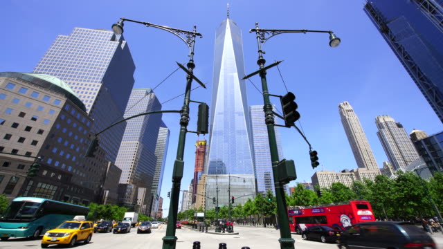one world trade center and the other lower manhattan skyscrapers stand behind traffic signals new york. 9/11 memorial at the right and world financial center at the left. cars run on the west side highway. - one world trade center stock-videos und b-roll-filmmaterial