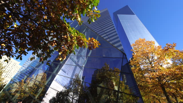tu one world trade center reflects to 9/11 memorial museum exterior wall which surrounded by autumn color trees. - memorial stock videos & royalty-free footage