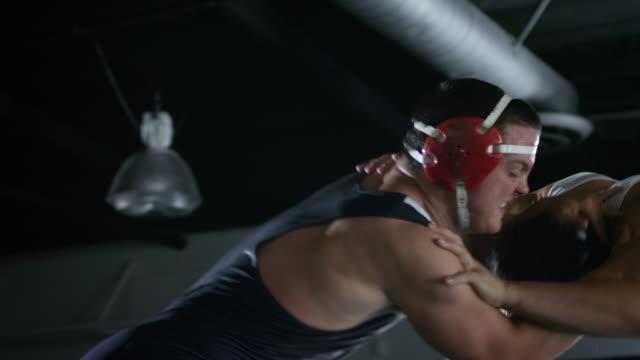 ms td slo mo one wrestler is taken down into headlock in wrestling match / riverside, california, united states - レスリング点の映像素材/bロール