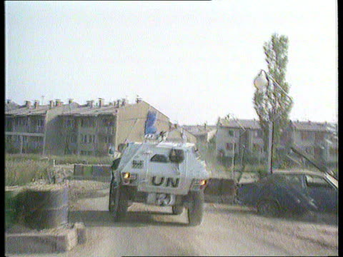 one year after start of civil war; tx 23.7.92 bv un apc along past wrecked buildings track forward - bosnian war stock videos & royalty-free footage