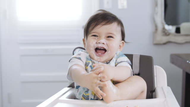 one year old baby boy sitting in his high chair playing with his food while playing with his feet with food - pulling funny faces stock videos & royalty-free footage