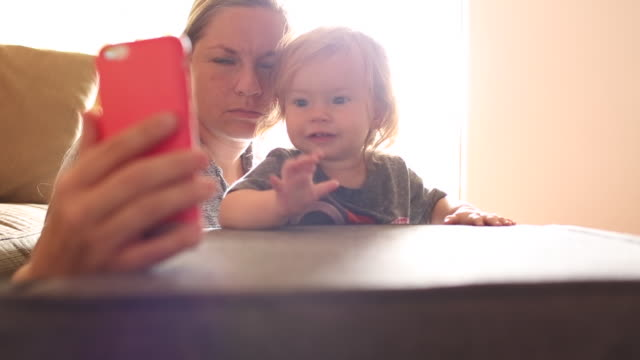 vídeos de stock, filmes e b-roll de a one year old baby girl and her mother talking together on a cellular phone with a friend or family member. - voip