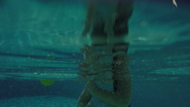 A one year old baby girl being dunked under water inside of a pool.