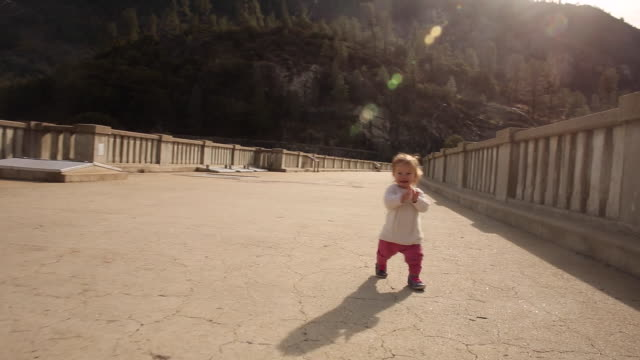 vidéos et rushes de a one year old baby girl learning to walk outdoors in yosemite national park on a bridge. - se déplacer vers le bas