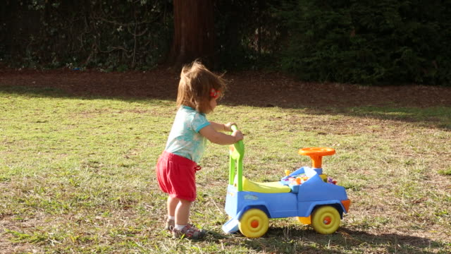 vidéos et rushes de a one year old baby girl playing outside in a park on a sunny day. - pushing