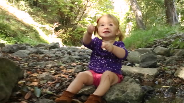 A one year old baby girl sitting and playing near a creek in a park.