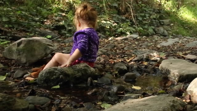 a one year old baby girl sitting and playing near a creek in a park. - one baby girl only stock videos & royalty-free footage