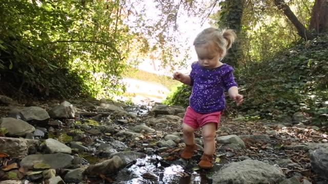 vídeos de stock, filmes e b-roll de a one year old baby girl sitting and playing near a creek in a park. - vida de bebê