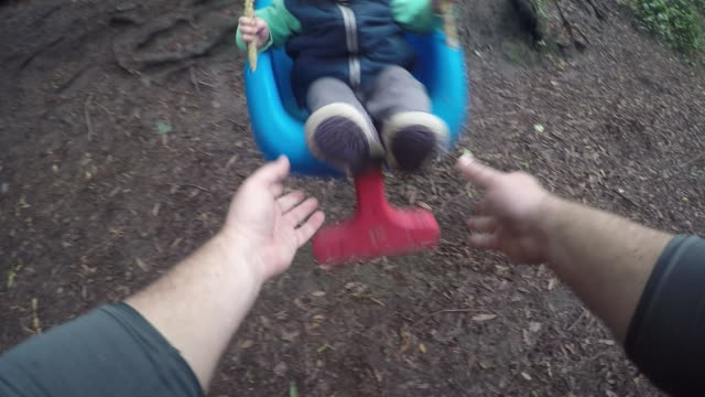 A one year old baby girl swinging in the arms of her father and on a swing outdoors.