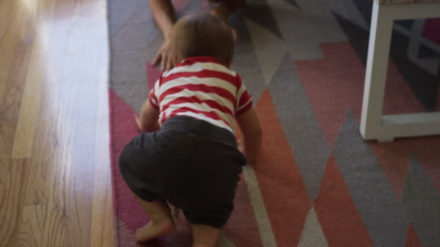 One year old baby, his mom, and dogs playing inside