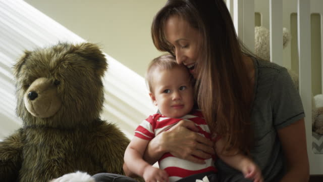 one year old baby, his mom, his dog and his giant teddy bear - 持ち上げる点の映像素材/bロール