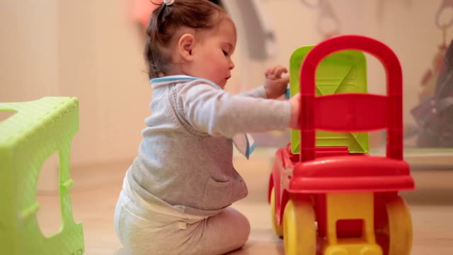 one year old baby playing with baby push car