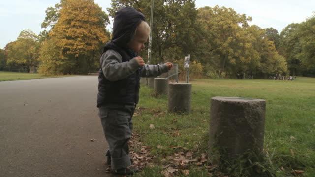 one year old boy trying to walk in the park - erste schritte stock-videos und b-roll-filmmaterial