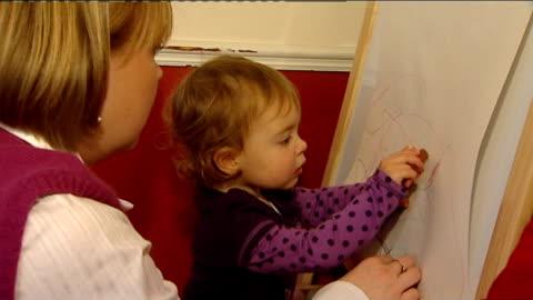 one year old girl has ground breaking surgery using calf's jugular vein; megan mills drawing on board and eating biscuit - människoådra bildbanksvideor och videomaterial från bakom kulisserna