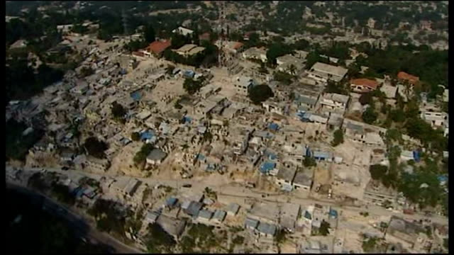 port au prince ext shots of digger clearing rubble from bank destroyed in earthquake in january 2010 views / aerials over wrecked and destroyed... - hispaniola stock videos & royalty-free footage