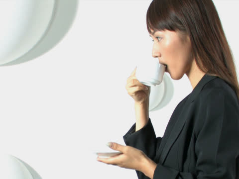 one young business woman is drinking a cup of coffee - tjänstekvinna bildbanksvideor och videomaterial från bakom kulisserna