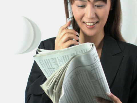 One young business woman is on the phone with reading the newspaper
