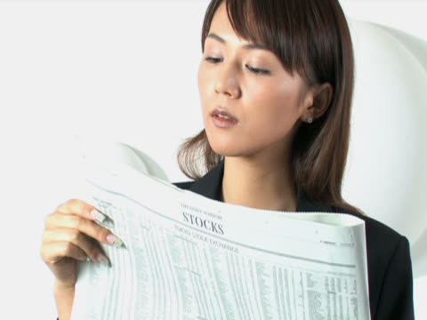 One young business woman is reading the newspaper