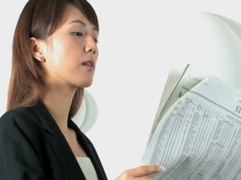 one young business woman is reading the newspaper - 若い女性点の映像素材/bロール