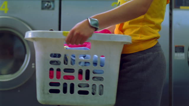 ms pan one young lady coming near by laundry machine with basket in hand /new york, new york, united states - inarcare la schiena video stock e b–roll
