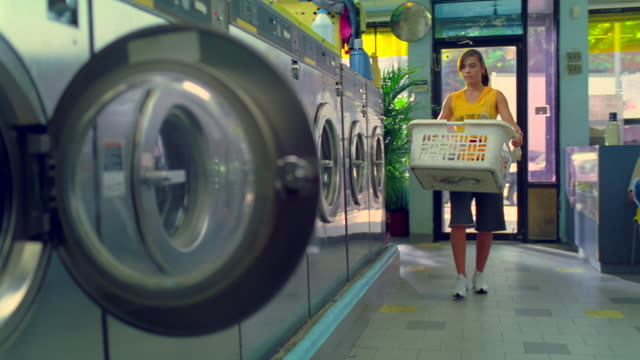 ms pan one young lady coming near by laundry machine with basket in hand/new york, new york, united states - waschsalon stock-videos und b-roll-filmmaterial