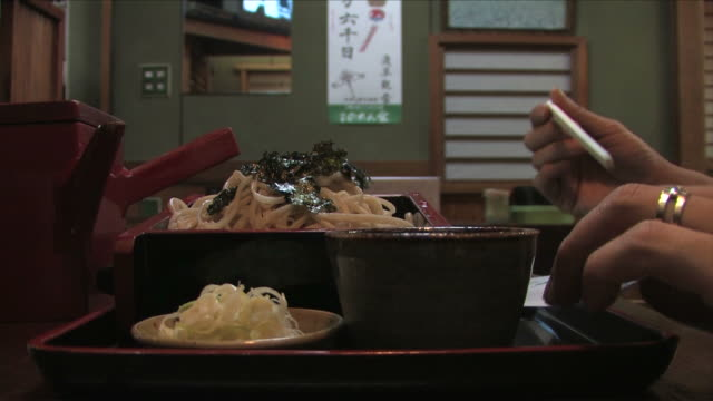 one young man is eating japanese noodle - soba stock videos & royalty-free footage