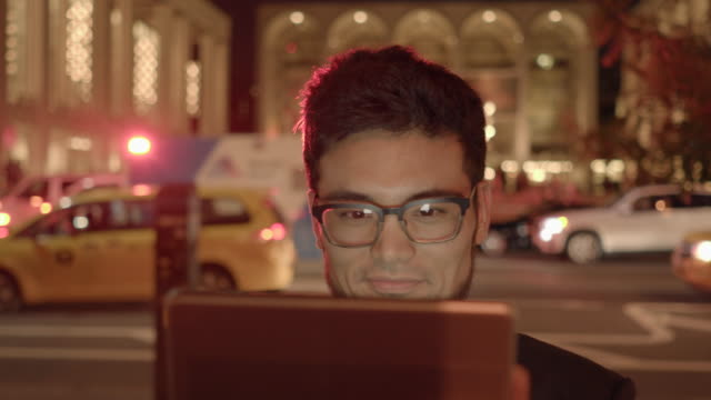 one young man with glasses looking at tablet computer screen browsing the internet in the city at night - goatee stock videos & royalty-free footage