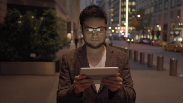 one young succesful asian man searching the internet on digital mobil tablet computer on city street at night - goatee stock videos & royalty-free footage
