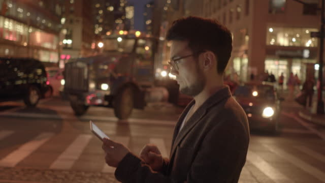 vidéos et rushes de one young succesful asian man searching the internet on digital mobil tablet computer on city street at night - profil