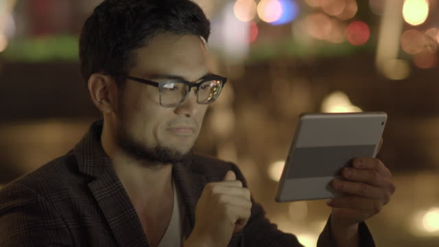one young succesful asian man searching the internet on digital mobil tablet computer on city street at night - ziegenbart stock-videos und b-roll-filmmaterial