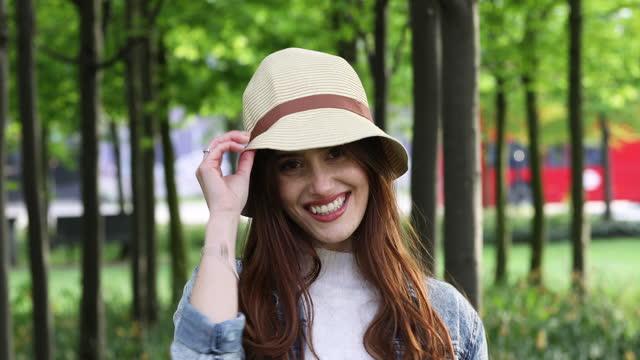 eine junge frau in einem stadtpark im sommer, die einen hut aufsetzt, in die kamera schaut und lächelt, als ein roter londoner bus in die ferne fährt. - hut stock-videos und b-roll-filmmaterial
